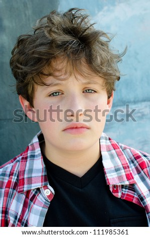 Young boy looking sadly into the camera - stock photo