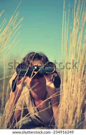 Young boy looking through binocular, low angle view  - stock photo