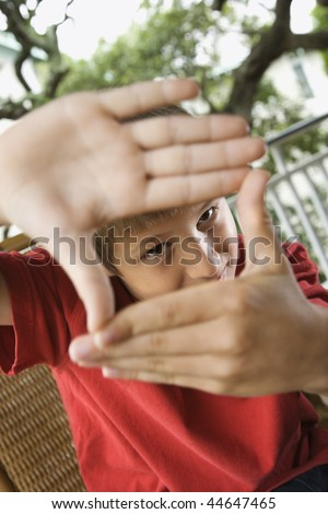 Young boy looking through hands at viewer. - stock photo
