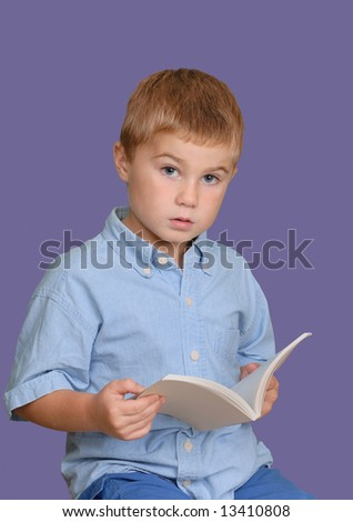 Young boy looking up from his book - stock photo