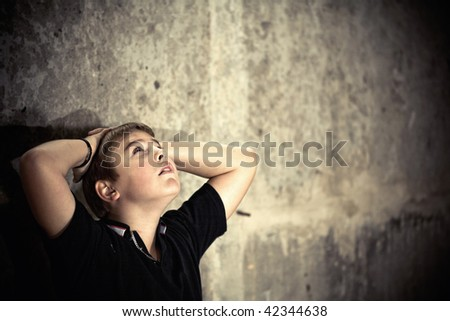 Young boy looking up with hope in his eyes against grunge background flash lit 3 light sources - stock photo