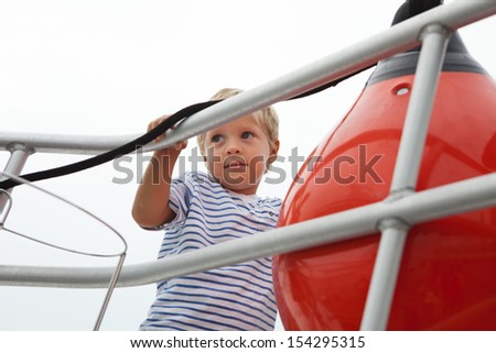 Young boy looks out from front of yacht
