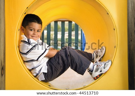 Young boy lying in crawl tube at playground. Horizontally framed shot. - stock photo