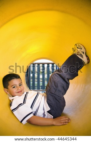 Young boy lying in crawl tube at playground. Vertically framed shot. - stock photo