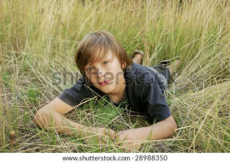 Young boy lying in tall grass - stock photo