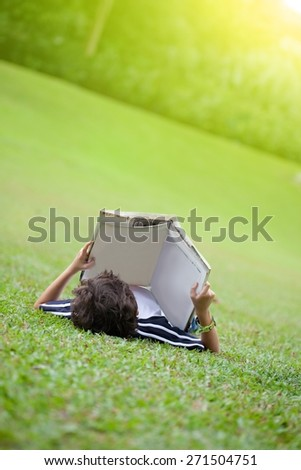 Young boy lying on open park reading a book - stock photo
