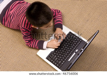 Young boy lying on the floor playing computer games - stock photo