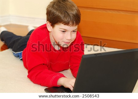 Young boy lying on the floor with portable computer