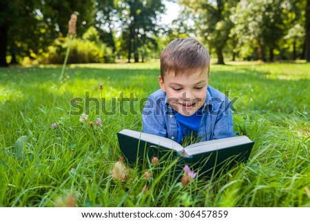 young boy lying on the meadow with book - stock photo
