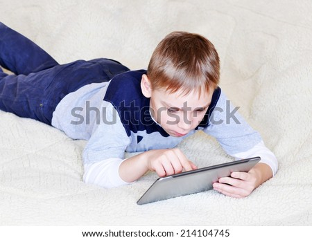 Young boy lying with digital tablet in a bed, playing - stock photo
