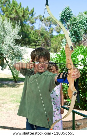 young boy makes archery