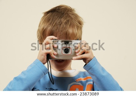 Young boy making photo with pocket camera - stock photo