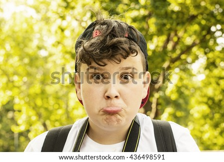 Young boy making the crazy face. Positive emotions. Funny youngster posing in nature. Pouting lips. - stock photo