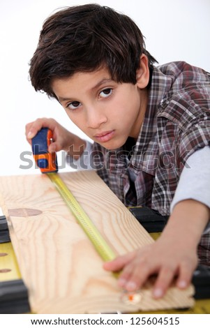 Young boy measuring a plank of wood - stock photo