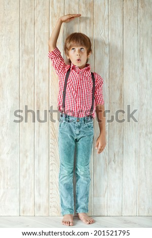 Young boy measuring his growth in height
