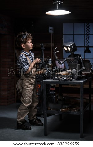 Young boy mechanic starts the robot in his workshop - stock photo