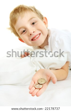 Young boy, missing a tooth, holding money from the tooth fairy (focus is on hand) - stock photo