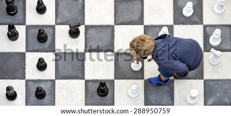 Young boy moving a white pawn during a chess game on an outdoor chess board, seen from above