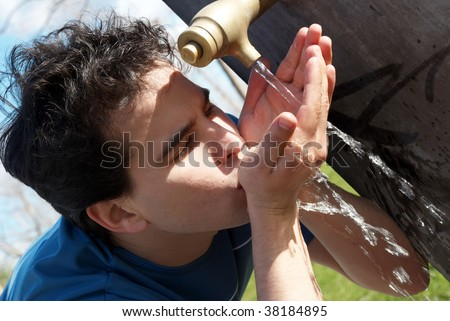 Young boy near a Drinking Fountain with water in park - stock photo