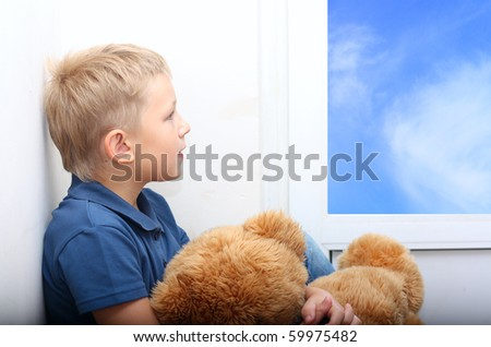 Young boy near window holding in hands teddy bear. - stock photo