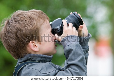 Young boy, nine years old, already practicing with an SLR shooting pictures of nature. - stock photo
