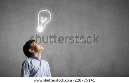 Young boy of school age looking up at light bulb