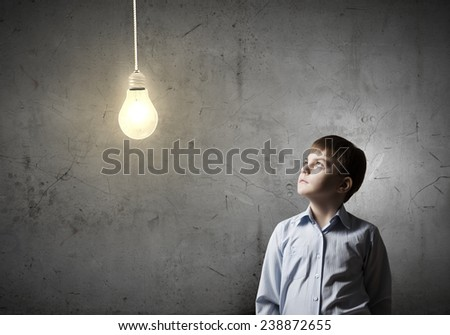 Young boy of school age looking up at light bulb - stock photo