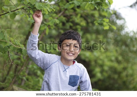 Young boy on a fence in a woodland - shallow depth of field, copy-space - stock photo