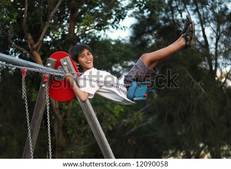 Young boy on a swing - stock photo