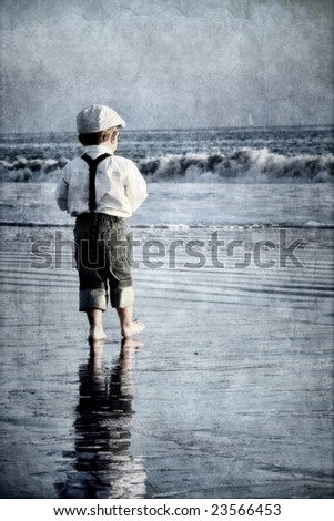 Young boy on beach looking at sailboat - stock photo