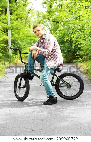 Young boy on BMX bike at park - stock photo