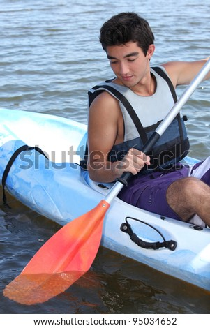 young boy on boat paddling - stock photo