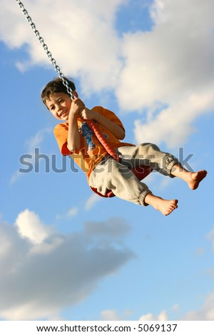 Young boy on chain swing, having fun in the evening sun against lovely blue sky.