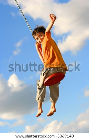 Young boy on chain swing raising one arm in excitement being lifted high.