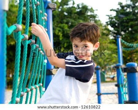 Young boy on climbing rope in playground - stock photo