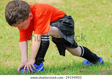 young boy on field stretching before soccer game - stock photo