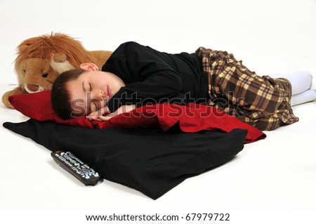 Young boy on pillows on the floor, fallen asleep watching television - stock photo