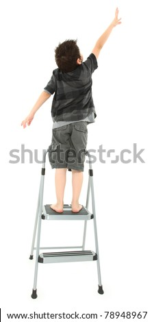 Young boy on step ladder reaching up over white background. - stock photo