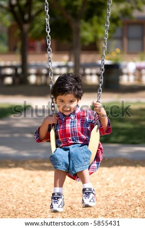 Young Boy on swing stares intently into the camera - stock photo