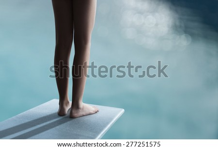 Young boy or girl is standing on a divingboard - stock photo