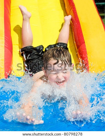 Young boy or kid has fun splashing into pool after going down water slide during summer - stock photo