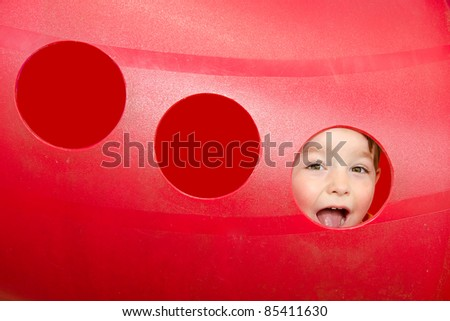 Young boy or kid playing in red tunnel outdoors on playground - stock photo