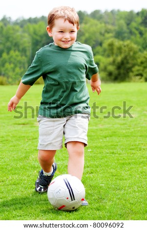 Young boy or kid plays soccer or football sports for exercise and activity. - stock photo