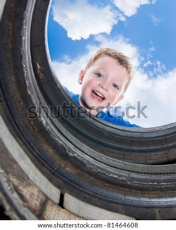 Young boy or kid smiles while playing at playground at park during spring or summer. - stock photo