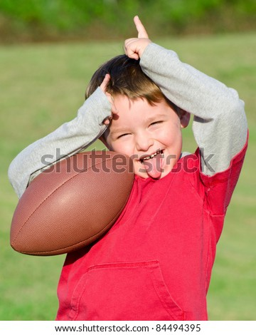 Young boy or kid with football celebrating or trash talking after scoring - stock photo