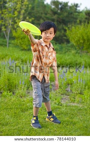 Young boy outdoor activity: playing frisbee - stock photo