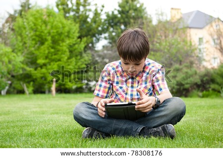 Young boy outdoors on the grass at backyard using his tablet computer. Educating and playing - stock photo