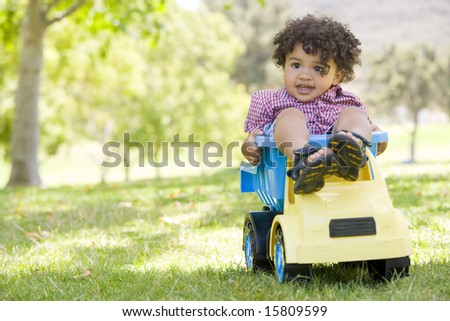 Young boy outdoors playing on toy dump truck smiling - stock photo