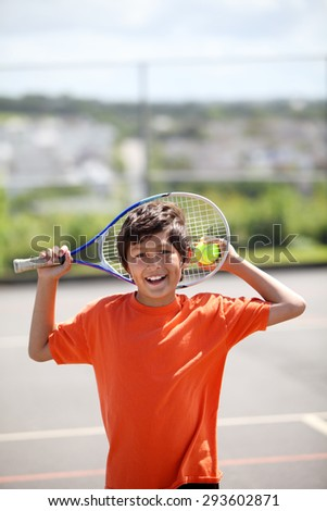 Young boy outside in sun with tennis racquet and ball - portrait format with copy space above - stock photo