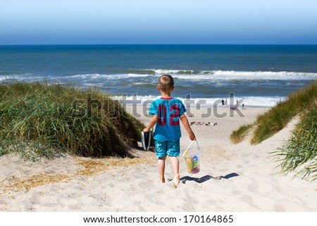 Young boy overlooking horizon over water and walking through eroded sand dunes on his way to a beach in Northern Europe during summer time. Boy is carrying his plastic toys for water play. - stock photo